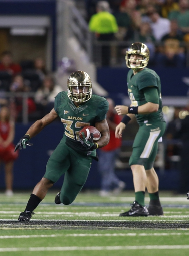 Nov 16, 2013; Arlington, TX, USA; Baylor Bears running back Shock Linwood (32) runs the ball while  quarterback Bryce Petty (14) watches in the fourth quarter of the game against the Texas Tech Red Raiders at AT&T Stadium.  Baylor beat Texas Tech 63-34. Mandatory Credit: Tim Heitman-USA TODAY Sports