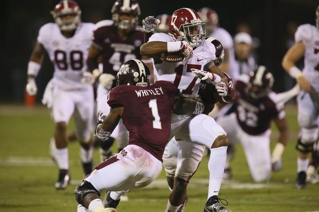 Nov 16, 2013; Starkville, MS, USA; Alabama Crimson Tide running back Kenyan Drake (17) advances the ball and is hit by Mississippi State Bulldogs defensive back Nickoe Whitley (1) during the game at Davis Wade Stadium. Alabama Crimson Tide defeat the Mississippi State Bulldogs with a score of 20-7.  Mandatory Credit: Spruce Derden-USA TODAY Sports