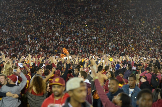 Nov 16, 2013; Los Angeles, CA, USA; Southern California Trojans fans storm the field after the game against the Stanford Cardinal at Los Angeles Memorial Coliseum. USC defeated Stanford 20-17. Mandatory Credit: Kirby Lee-USA TODAY Sports
