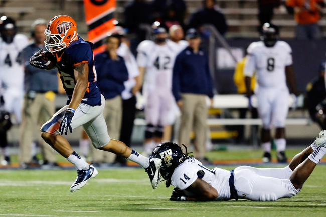 Nov 16, 2013; El Paso, TX, USA; UTEP Miners running back Nathan Jeffery (25) breaks a tackle from FIU Golden Panthers safety Demarkus Perkins (14) and runs in for a touchdown at Sun Bowl Stadium. Mandatory Credit: Ivan Pierre Aguirre-USA TODAY Sports