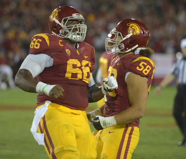 Nov 16, 2013; Los Angeles, CA, USA; Southern California Trojans center Marcus Martin (66) and defensive end J.R. Tavai (58) celebrate after a 47-yard field goal by Andre Heidari (not pictured) with 19 seconds left against the Stanford Cardinal at Los Angeles Memorial Coliseum. USC defeated Stanford 20-17. Mandatory Credit: Kirby Lee-USA TODAY Sports