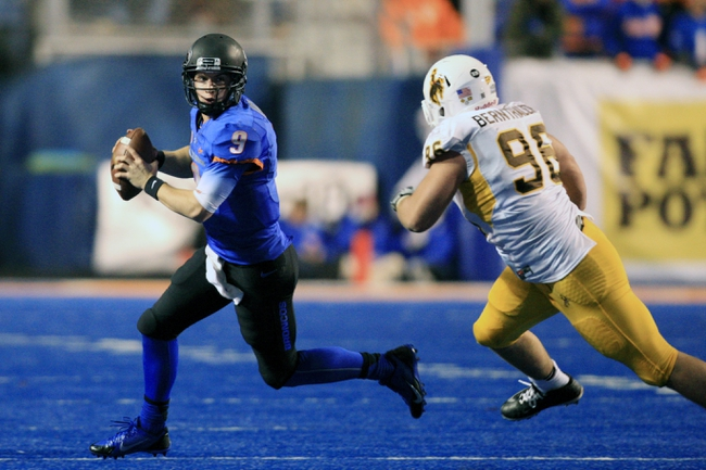 Nov 16, 2013; Boise, ID, USA; Boise State Broncos quarterback Grant Hedrick (9) scrambles away from Wyoming Cowboys defensive tackle Justin Bernthaler (96) during the second half  at Bronco Stadium. Boise State defeated Wyoming 48-7. Mandatory Credit: Brian Losness-USA TODAY Sports