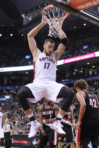 Nov 17, 2013; Toronto, Ontario, CAN; Toronto Raptors center Jonas Valanciunas (17) holds onto the rim after baking a dunk shot during the fourth quarter of a game at the Air Canada Centre. Portland won the game 118-110. Mandatory Credit: Mark Konezny-USA TODAY Sports