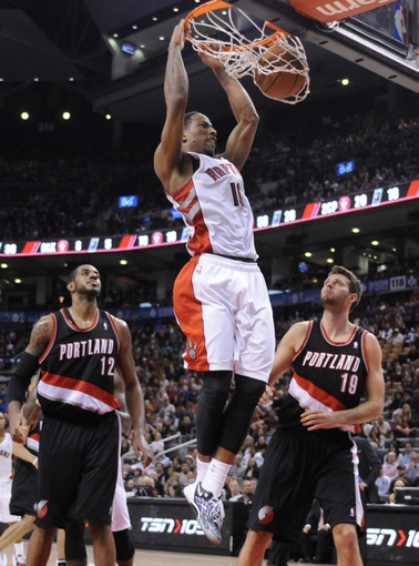 Nov 17, 2013; Toronto, Ontario, CAN; Toronto Raptors shooting guard DeMar DeRozan (10) makes a dunk shot with Portland Trail Blazers power forward LaMarcus Aldridge (12) and center Joel Freeland (19) looking on during the fourth quarter of a game at the Air Canada Centre. Portland won the game 118-110. Mandatory Credit: Mark Konezny-USA TODAY Sports