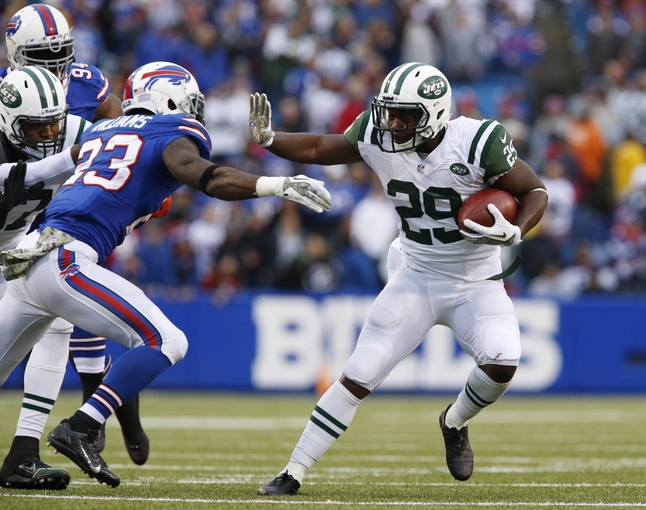 Nov 17, 2013; Orchard Park, NY, USA; New York Jets running back Bilal Powell (29) straight arms Buffalo Bills free safety Aaron Williams (23) on a run during the second half at Ralph Wilson Stadium. Bills beat the Jets 37-14. Mandatory Credit: Kevin Hoffman-USA TODAY Sports