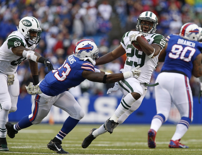 Nov 17, 2013; Orchard Park, NY, USA; New York Jets running back Bilal Powell (29) breaks a tackle by Buffalo Bills free safety Aaron Williams (23) during the second half at Ralph Wilson Stadium. Bills beat the Jets 37-14. Mandatory Credit: Kevin Hoffman-USA TODAY Sports