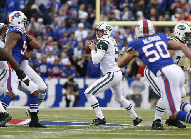 Nov 17, 2013; Orchard Park, NY, USA; New York Jets quarterback Matt Simms (5) drops to pass under pressure from Buffalo Bills middle linebacker Kiko Alonso (50) and defensive end Mario Williams (94) during the second half at Ralph Wilson Stadium. Bills beat the Jets 37-14. Mandatory Credit: Kevin Hoffman-USA TODAY Sports