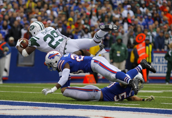 Nov 17, 2013; Orchard Park, NY, USA; New York Jets running back Bilal Powell (29) dives to try and get into the end zone while being tackled by Buffalo Bills free safety Aaron Williams (23) and middle linebacker Kiko Alonso (50) during the second half at Ralph Wilson Stadium. Bills beat the Jets 37-14.  Mandatory Credit: Timothy T. Ludwig-USA TODAY Sports