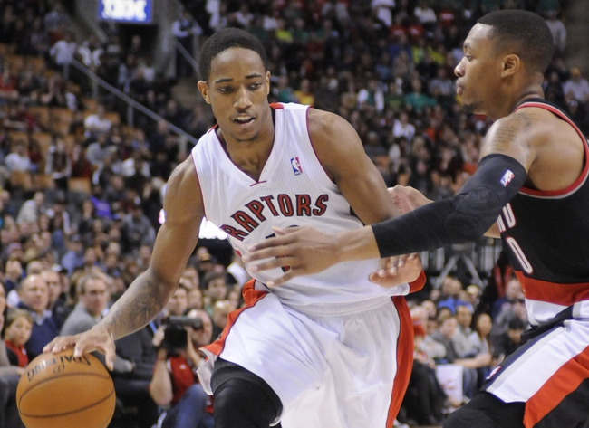 Nov 17, 2013; Toronto, Ontario, CAN; Toronto Raptors shooting guard DeMar DeRozan (10) tries to get past Portland Trail Blazers point guard Damian Lillard (0) during the fourth quarter of a game at the Air Canada Centre. Portland won the game 118-110. Mandatory Credit: Mark Konezny-USA TODAY Sports
