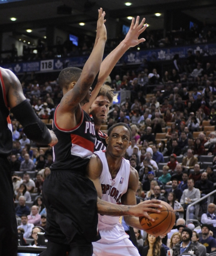 Nov 17, 2013; Toronto, Ontario, CAN; Toronto Raptors shooting guard DeMar DeRozan (10) tries to get a shot off against the defense of Portland Trail Blazers point guard Damian Lillard and center Robin Lopez (42) during the fourth quarter of a game at the Air Canada Centre. Portland won the game 118-110. Mandatory Credit: Mark Konezny-USA TODAY Sports