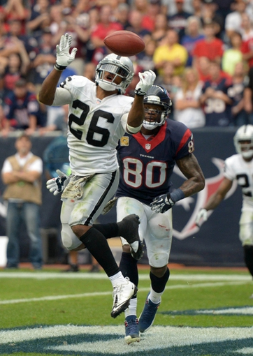Nov 17, 2013; Houston, TX, USA; Oakland Raiders safety Usama Young (26) breaks up a pass intended for Houston Texans receiver Andre Johnson (80) in the end zone with 1:10 to play at Reliant Stadium. The Raiders defeated the Texans 28-23. Mandatory Credit: Kirby Lee-USA TODAY Sports
