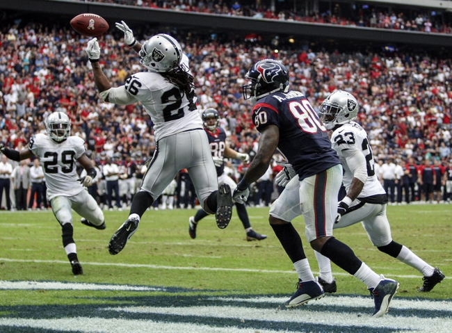Nov 17, 2013; Houston, TX, USA; Oakland Raiders free safety Usama Young (26) attempts to intercept a pass intended for Houston Texans wide receiver Andre Johnson (80) during the fourth quarter at Reliant Stadium. The Raiders defeated the Texans 28-23. Mandatory Credit: Troy Taormina-USA TODAY Sports