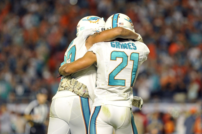 Nov 17, 2013; Miami Gardens, FL, USA; Miami Dolphins safety Jimmy Wilson (27) and Miami Dolphins cornerback Brent Grimes (21) celebrate a win over the San Diego Chargers after the second half at Sun Life Stadium. The Dolphins won the game 20-16. Mandatory Credit: Joe Camporeale-USA TODAY Sports