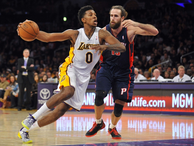 November 17, 2013; Los Angeles, CA, USA; Los Angeles Lakers small forward Nick Young (0) moves the ball against the defense of Detroit Pistons small forward Luigi Datome (13) during the second half at Staples Center. Mandatory Credit: Gary A. Vasquez-USA TODAY Sports