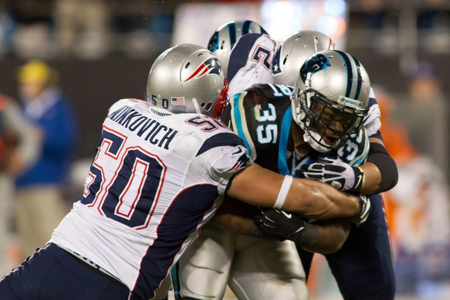 Nov 18, 2013; Charlotte, NC, USA; Carolina Panthers fullback Mike Tolbert (35) gets tackled by New England Patriots defensive end Rob Ninkovich (50) during the fourth quarter at Bank of America Stadium. The Panthers defeated the Patriots 24-20. Mandatory Credit: Jeremy Brevard-USA TODAY Sports