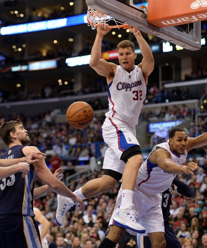 Nov 18, 2013; Los Angeles, CA, USA; Los Angeles Clippers power forward Blake Griffin (32) dunks off of a missed shot over Memphis Grizzlies center Marc Gasol (33) and teammate Ryan Hollins (right) during second half action at Staples Center. The Grizzlies went on to a 106-102 win. Griffin had 23 points in the game. Mandatory Credit: Robert Hanashiro-USA TODAY Sports