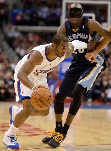 Nov 18, 2013; Los Angeles, CA, USA; Los Angeles Clippers point guard Chris Paul (3) dribbles past Memphis Grizzlies small forward Quincy Pondexter (20) during third quarter action at Staples Center. Mandatory Credit: Robert Hanashiro-USA TODAY Sports