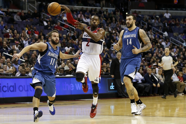 Nov 19, 2013; Washington, DC, USA; Washington Wizards point guard John Wall (2) passes the ball as Minnesota Timberwolves point guard J.J. Barea (11) and center Nikola Pekovic (14) chase in the second quarter at Verizon Center. Mandatory Credit: Geoff Burke-USA TODAY Sports