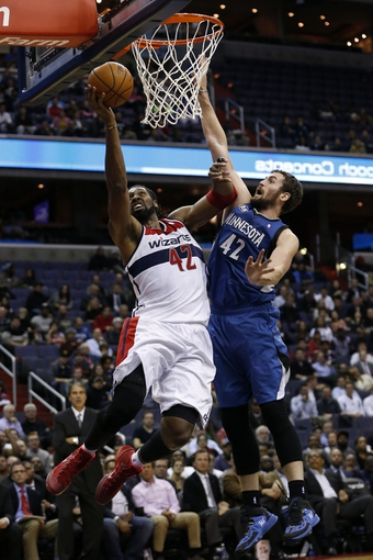 Nov 19, 2013; Washington, DC, USA; Washington Wizards power forward Nene Hilario (42) shoots the ball over Minnesota Timberwolves power forward Kevin Love (42) in the second quarter at Verizon Center. Mandatory Credit: Geoff Burke-USA TODAY Sports