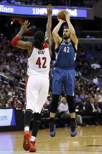 Nov 19, 2013; Washington, DC, USA; Minnesota Timberwolves power forward Kevin Love (42) shoots the ball over Washington Wizards power forward Nene Hilario (42) in the third quarter at Verizon Center. The Wizards won 104-100. Mandatory Credit: Geoff Burke-USA TODAY Sports