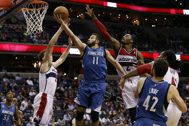 Nov 19, 2013; Washington, DC, USA; Minnesota Timberwolves point guard J.J. Barea (11) shoots the ball as Washington Wizards power forward Jan Vesely (24) and Wizards point guard John Wall (2) defend in the fourth quarter at Verizon Center. The Wizards won 104-100. Mandatory Credit: Geoff Burke-USA TODAY Sports