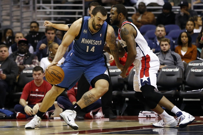 Nov 19, 2013; Washington, DC, USA; Minnesota Timberwolves center Nikola Pekovic (14) dribbles the ball as Washington Wizards power forward Trevor Booker (35) defends in the second quarter at Verizon Center. The Wizards won 104-100. Mandatory Credit: Geoff Burke-USA TODAY Sports