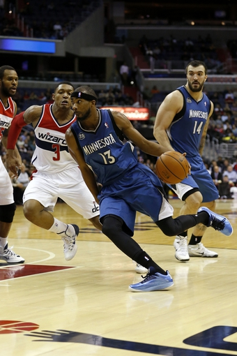 Nov 19, 2013; Washington, DC, USA; Minnesota Timberwolves small forward Corey Brewer (13) dribbles the ball past Washington Wizards shooting guard Bradley Beal (3) in the fourth quarter at Verizon Center. The Wizards won 104-100. Mandatory Credit: Geoff Burke-USA TODAY Sports