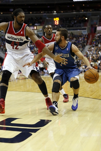 Nov 19, 2013; Washington, DC, USA; Minnesota Timberwolves point guard J.J. Barea (11) dribbles the ball as Washington Wizards power forward Nene Hilario (42) and Wizards point guard John Wall (2) defend in the fourth quarter at Verizon Center. The Wizards won 104-100. Mandatory Credit: Geoff Burke-USA TODAY Sports