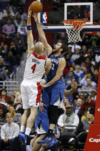 Nov 19, 2013; Washington, DC, USA; Washington Wizards center Marcin Gortat (4) shoots the ball as Minnesota Timberwolves power forward Kevin Love (42) defends in the fourth quarter at Verizon Center. The Wizards won 104-100. Mandatory Credit: Geoff Burke-USA TODAY Sports