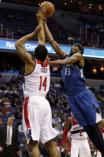 Nov 19, 2013; Washington, DC, USA; Minnesota Timberwolves small forward Corey Brewer (13) shoots the ball over Washington Wizards shooting guard Glen Rice Jr. (14) in the third quarter at Verizon Center. The Wizards won 104-100. Mandatory Credit: Geoff Burke-USA TODAY Sports