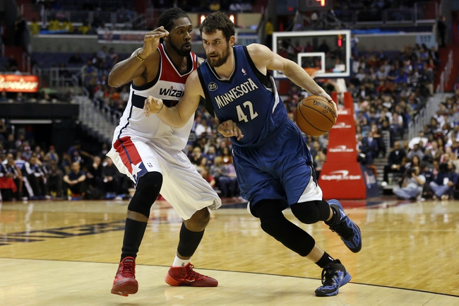 Nov 19, 2013; Washington, DC, USA; Minnesota Timberwolves power forward Kevin Love (42) dribbles the ball as Washington Wizards power forward Nene Hilario (42) defends in the fourth quarter at Verizon Center. The Wizards won 104-100. Mandatory Credit: Geoff Burke-USA TODAY Sports