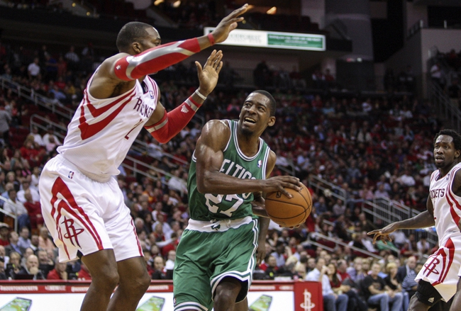 Nov 19, 2013; Houston, TX, USA; Boston Celtics shooting guard Jordan Crawford (27) drives the ball to the basket during the third quarter as Houston Rockets power forward Dwight Howard (12) defends at Toyota Center. Mandatory Credit: Troy Taormina-USA TODAY Sports