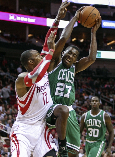 Nov 19, 2013; Houston, TX, USA; Boston Celtics shooting guard Jordan Crawford (27) drives to the basket during the third quarter as Houston Rockets power forward Dwight Howard (12) defends at Toyota Center. Mandatory Credit: Troy Taormina-USA TODAY Sports