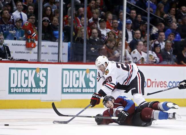 Nov 19, 2013; Denver, CO, USA; Colorado Avalanche center Nathan MacKinnon (29) clears the puck out as he slides in front of Chicago Blackhawks left wing Brandon Saad (20) during the second period at Pepsi Center. Mandatory Credit: Chris Humphreys-USA TODAY Sports