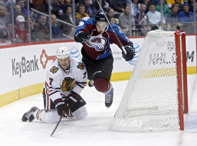 Nov 19, 2013; Denver, CO, USA; Colorado Avalanche center Nathan MacKinnon (29) dives to steal the puck away from Chicago Blackhawks defenseman Brent Seabrook (7) during the second period at Pepsi Center. Mandatory Credit: Chris Humphreys-USA TODAY Sports