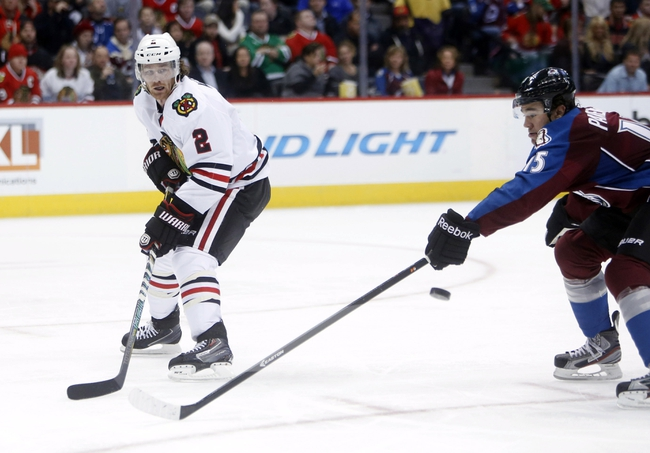 Nov 19, 2013; Denver, CO, USA; Chicago Blackhawks defenseman Duncan Keith (2) passes the puck by Colorado Avalanche right wing PA Parenteau (15) during the second period at Pepsi Center. Mandatory Credit: Chris Humphreys-USA TODAY Sports