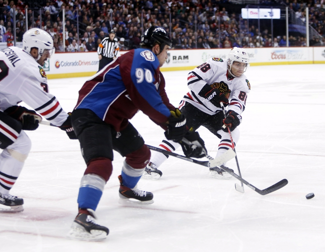 Nov 19, 2013; Denver, CO, USA; Chicago Blackhawks right wing Patrick Kane (88) passes the puck past Colorado Avalanche center Ryan O'Reilly (90) during the second period at Pepsi Center. Mandatory Credit: Chris Humphreys-USA TODAY Sports