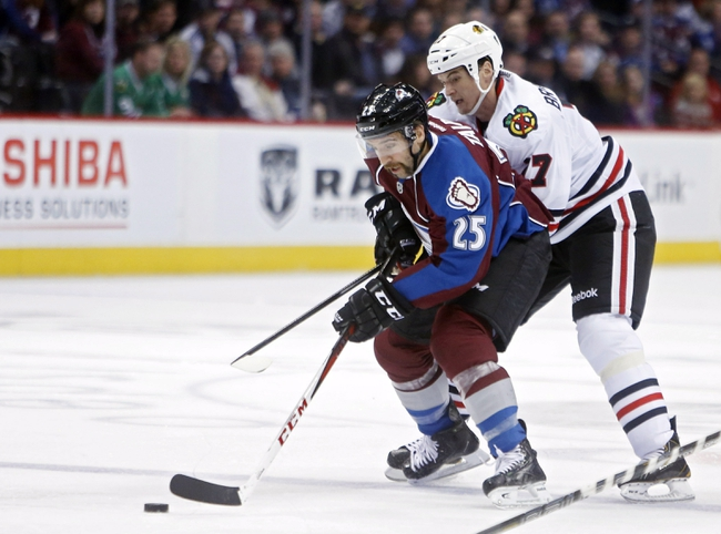 Nov 19, 2013; Denver, CO, USA; Colorado Avalanche center Maxime Talbot (25) controls the puck in front of Chicago Blackhawks defenseman Sheldon Brookbank (17) during the second period at Pepsi Center. Mandatory Credit: Chris Humphreys-USA TODAY Sports