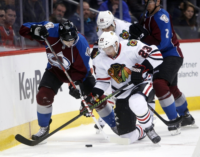 Nov 19, 2013; Denver, CO, USA; Colorado Avalanche center John Mitchell (7) battles Chicago Blackhawks right wing Kris Versteeg (23) for the puck during the third period at Pepsi Center. The Avalanche won 5-1. Mandatory Credit: Chris Humphreys-USA TODAY Sports