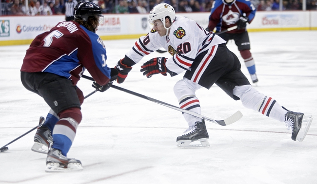 Nov 19, 2013; Denver, CO, USA; Chicago Blackhawks left wing Brandon Saad (20) takes the puck around Colorado Avalanche defenseman Nate Guenin (5) during the third period at Pepsi Center. The Avalanche won 5-1. Mandatory Credit: Chris Humphreys-USA TODAY Sports