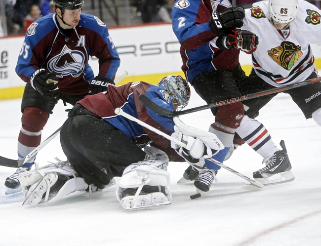 Nov 19, 2013; Denver, CO, USA; Colorado Avalanche goalie Semyon Varlamov (1) stops the puck in front of Chicago Blackhawks center Andrew Shaw (65) during the third period at Pepsi Center. The Avalanche won 5-1. Mandatory Credit: Chris Humphreys-USA TODAY Sports