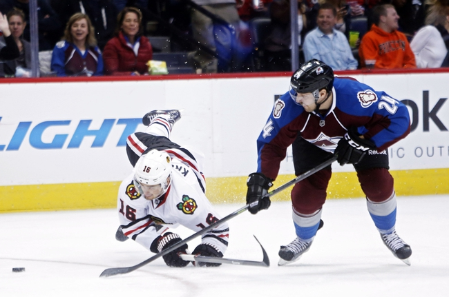 Nov 19, 2013; Denver, CO, USA; Colorado Avalanche center Marc-Andre Cliche (24) and Chicago Blackhawks center Marcus Kruger (16) battle for the puck during the third period at Pepsi Center. The Avalanche won 5-1. Mandatory Credit: Chris Humphreys-USA TODAY Sports