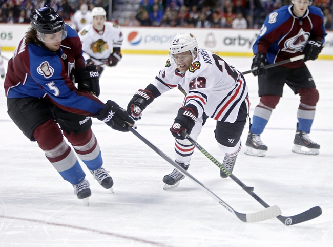 Nov 19, 2013; Denver, CO, USA; Colorado Avalanche defenseman Nate Guenin (5) and Chicago Blackhawks right wing Kris Versteeg (23) reach for the puck during the third period at Pepsi Center. The Avalanche won 5-1. Mandatory Credit: Chris Humphreys-USA TODAY Sports