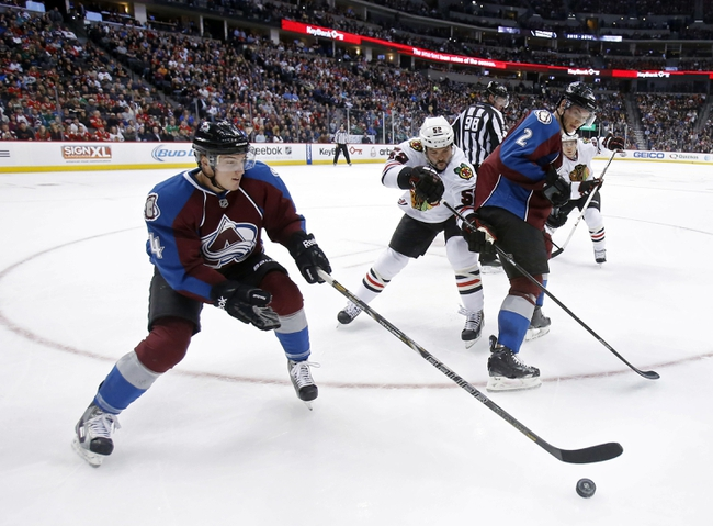 Nov 19, 2013; Denver, CO, USA; Colorado Avalanche defensemen Tyson Barrie (4) and Nick Holden (2) keep the puck away from Chicago Blackhawks left wing Brandon Bollig (52) during the third period at Pepsi Center. The Avalanche won 5-1. Mandatory Credit: Chris Humphreys-USA TODAY Sports