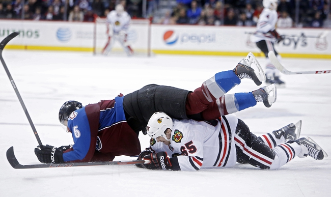Nov 19, 2013; Denver, CO, USA; Colorado Avalanche defenseman Erik Johnson (6) lands on top of Chicago Blackhawks center Andrew Shaw (65) during the third period at Pepsi Center. The Avalanche won 5-1. Mandatory Credit: Chris Humphreys-USA TODAY Sports