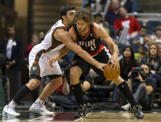 Nov 20, 2013; Milwaukee, WI, USA; Milwaukee Bucks center Zaza Pachulia (27) tries to knock the ball away from Portland Trail Blazers center Robin Lopez (42) during the third quarter at BMO Harris Bradley Center. Mandatory Credit: Jeff Hanisch-USA TODAY Sports