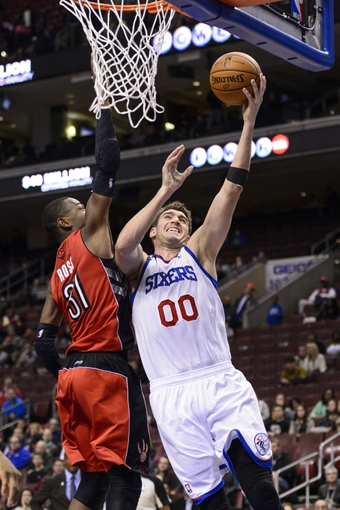 Nov 20, 2013; Philadelphia, PA, USA; Philadelphia 76ers center Spencer Hawes (00) shoots under pressure from Toronto Raptors guard Terrence Ross (31) during the fourth quarter at Wells Fargo Center. The Raptors defeated the Sixers 108-98. Mandatory Credit: Howard Smith-USA TODAY Sports
