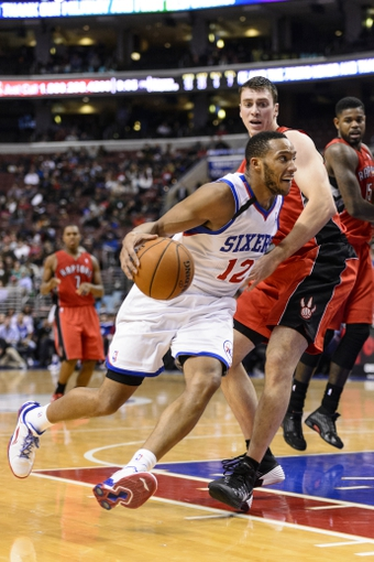 Nov 20, 2013; Philadelphia, PA, USA; Philadelphia 76ers guard Evan Turner (12) is defended by Toronto Raptors forward Tyler Hansbrough (50) during the fourth quarter at Wells Fargo Center. The Raptors defeated the Sixers 108-98. Mandatory Credit: Howard Smith-USA TODAY Sports