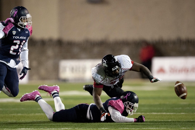 Nov 20, 2013; Toledo, OH, USA; Northern Illinois Huskies running back Cameron Stingily (42) drops the ball as he is tackled by Toledo Rockets defensive back Cheatham Norrils (11) during the fourth quarter at Glass Bowl. The Huskies beat the Rockets 35-17. Mandatory Credit: Raj Mehta-USA TODAY Sports
