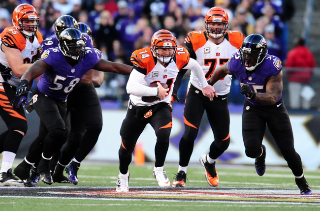 Nov 10, 2013; Baltimore, MD, USA; Cincinnati Bengals quarterback Andy Dalton (14) runs with the ball while being pressured by Baltimore Ravens linebackers Terrell Suggs (55) and Elvis Dumervil (58) at M&T Bank Stadium. Mandatory Credit: Evan Habeeb-USA TODAY Sports